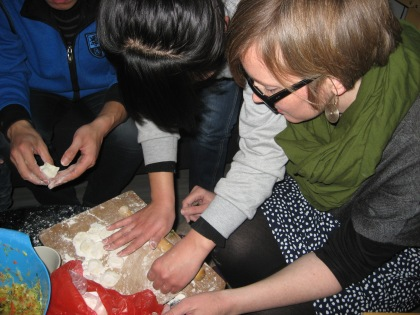 rolling out dough to make jiaozi wrappers