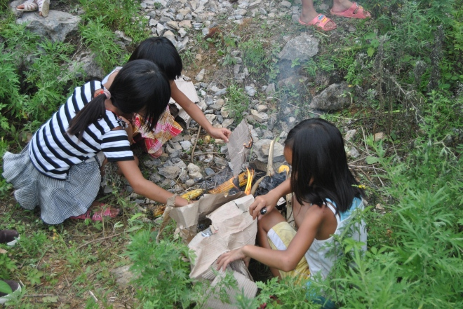 girls roasting corn