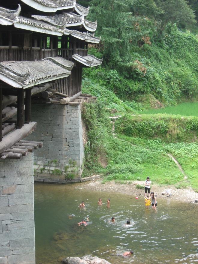 children swimming under a wooden bridge