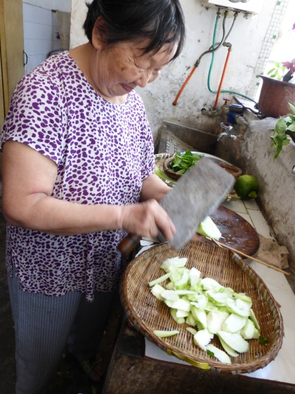 my friend's grandma roughly cutting si gua for lunch